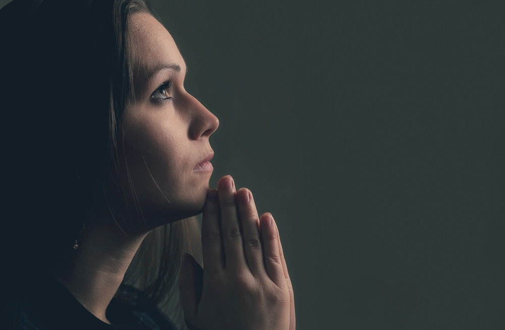 A woman holds her hands in prayer