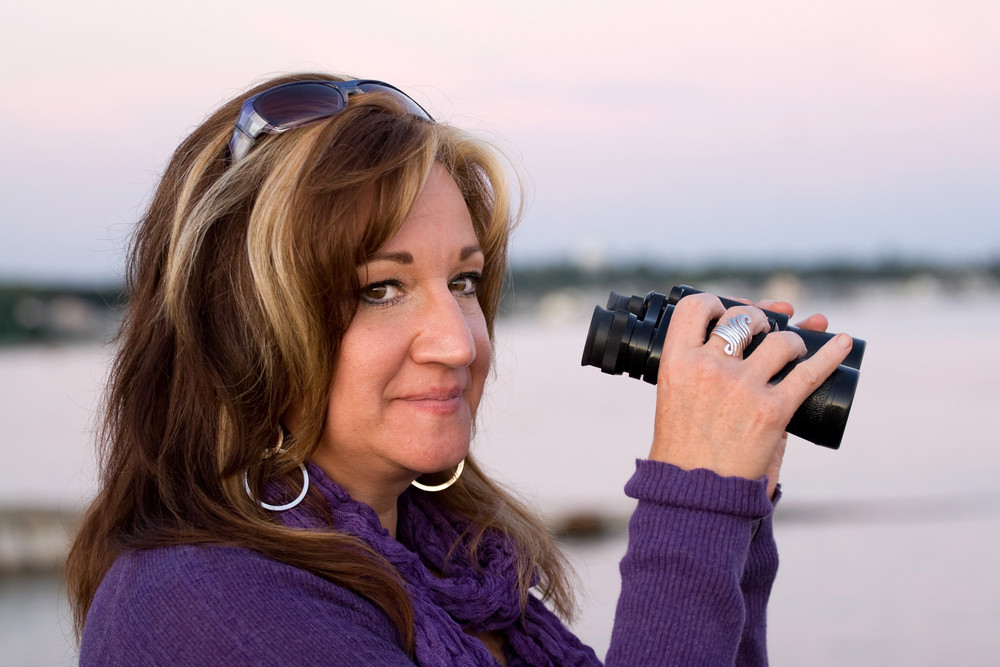 A woman looking with binoculars at the beach.