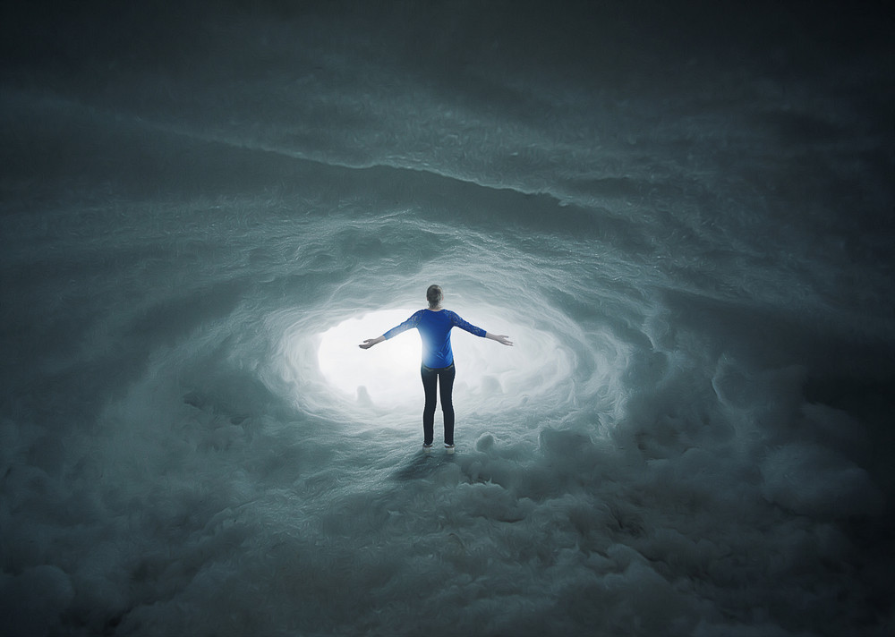 A woman lost in a snow cavern with her arms in praise.