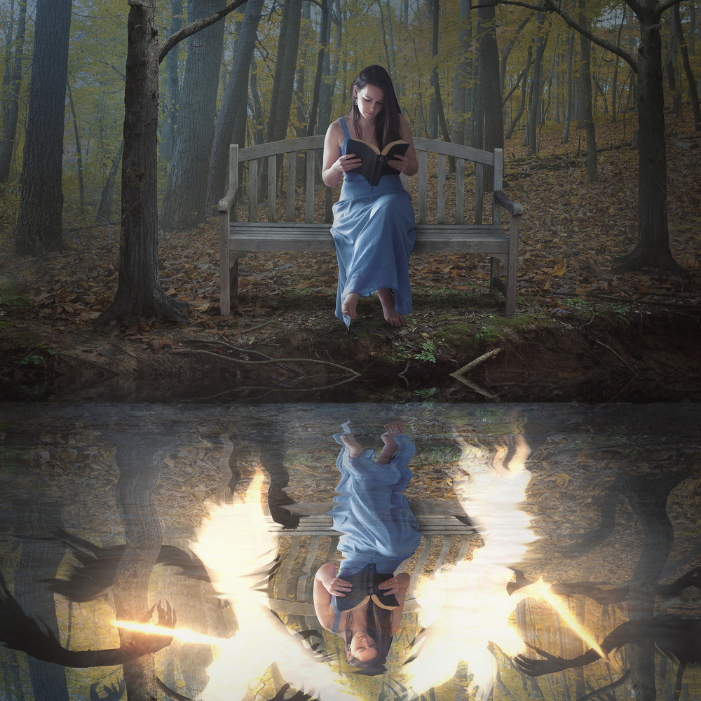 A woman reads her Bible alone while in the reflection angels and demons are fighting.
