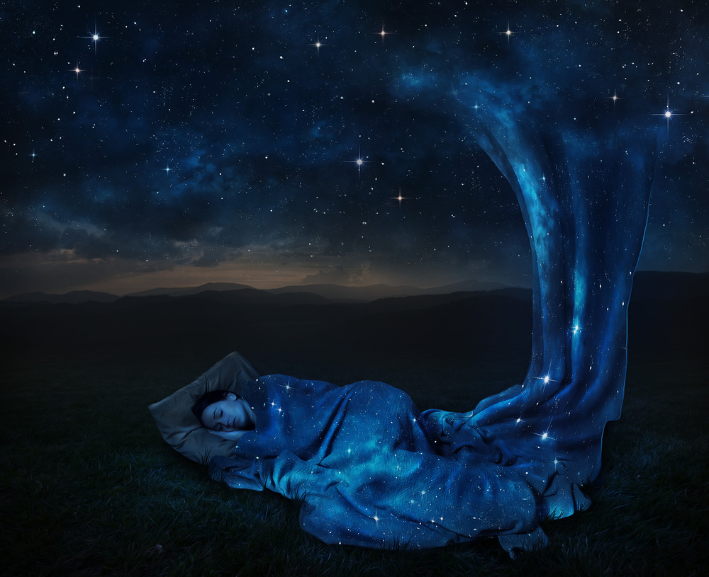 A woman sleeps under a blanket made of stars