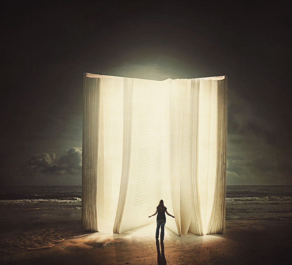 A woman stands in front of a tall glowing book