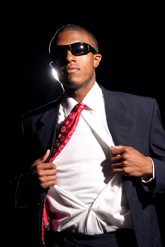A young African American business man ripping his shirt open to reveal the t-shirt beneath. Add your text or artwork to easily customize the message.