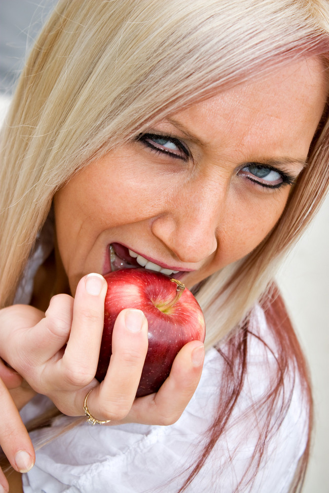 A young blonde woman biting into a bright red apple.