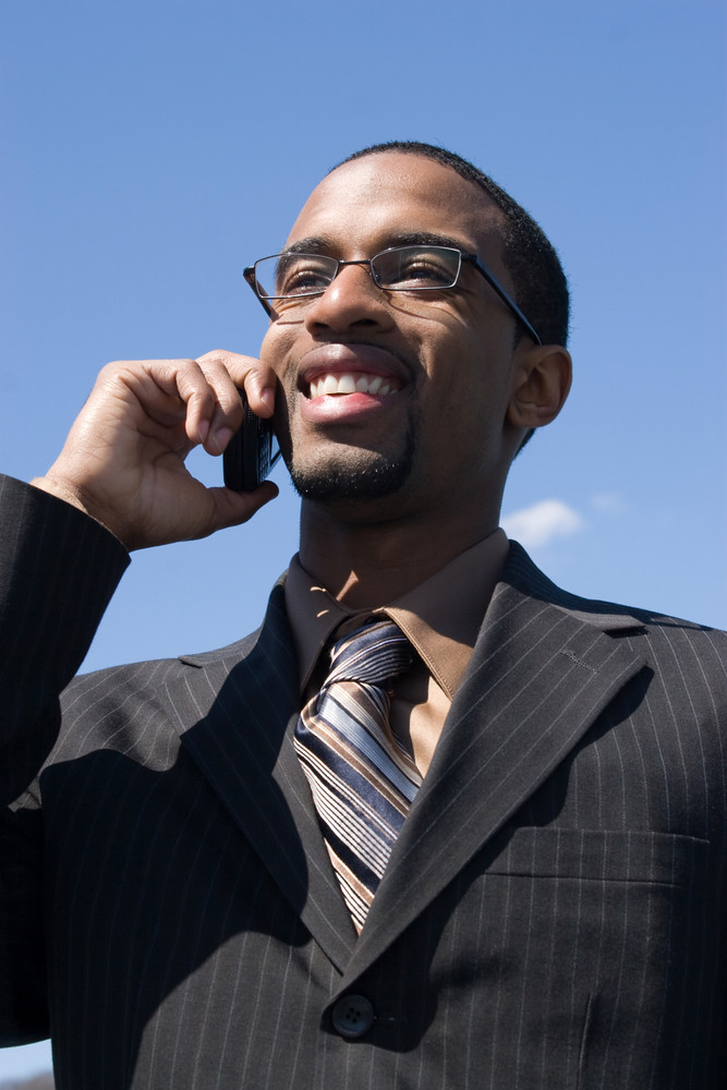 A young business professional talking on his wireless mobile phone.