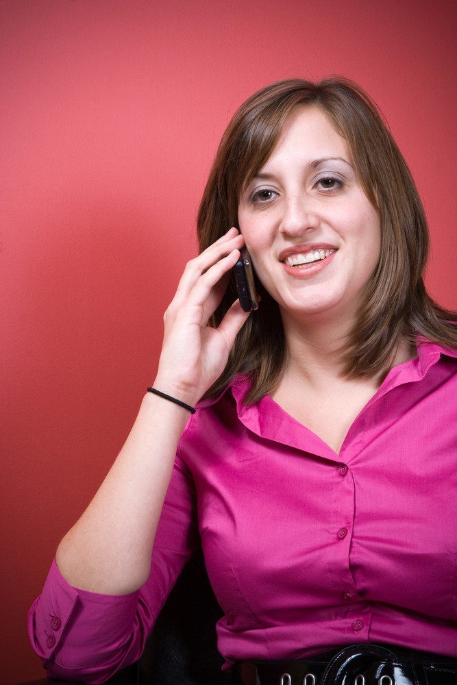 A young business woman talking on a cell phone while seated.