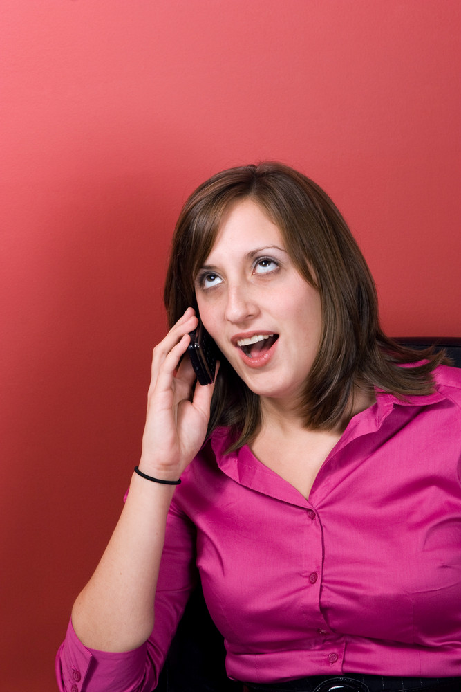 A young business woman talking on her cell phone at work.