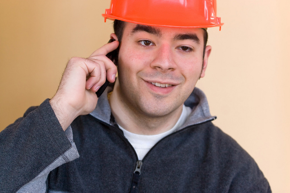 A young construction professional talks on his smartphone.