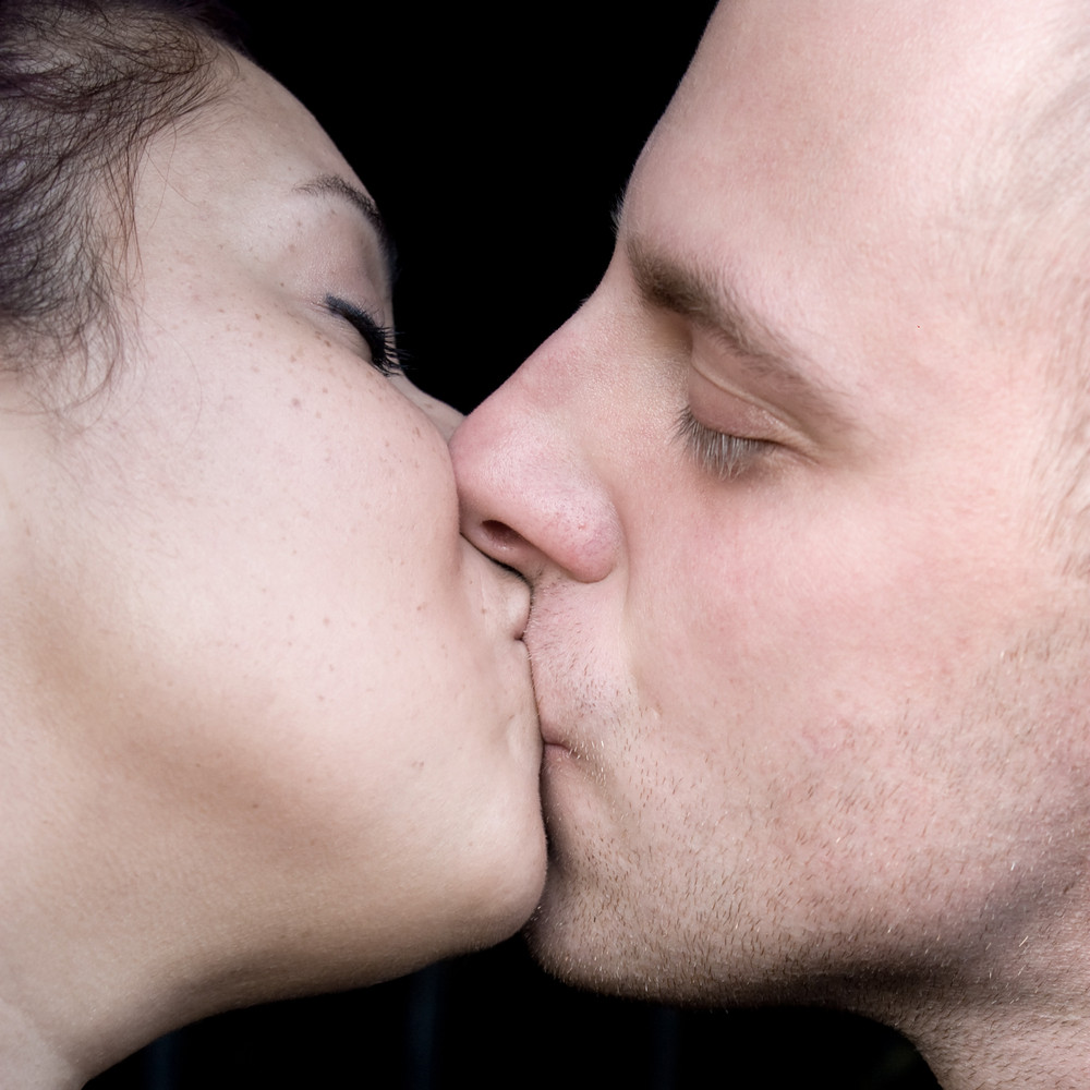 A young couple kissing each other.