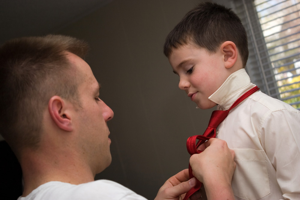 A young dad helps his son get ready by helping him tie his neck tie.