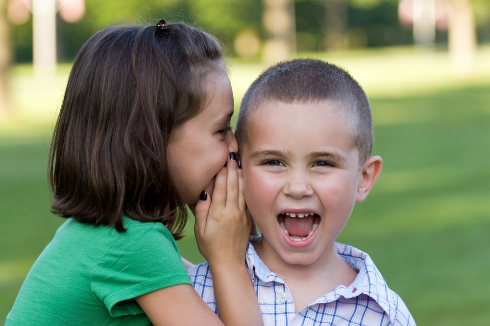 A young girl telling her brother a secret.