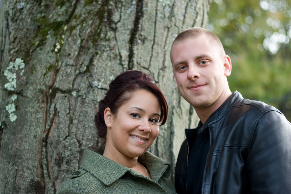 A young happy couple outdoor by a tree on a fall day.