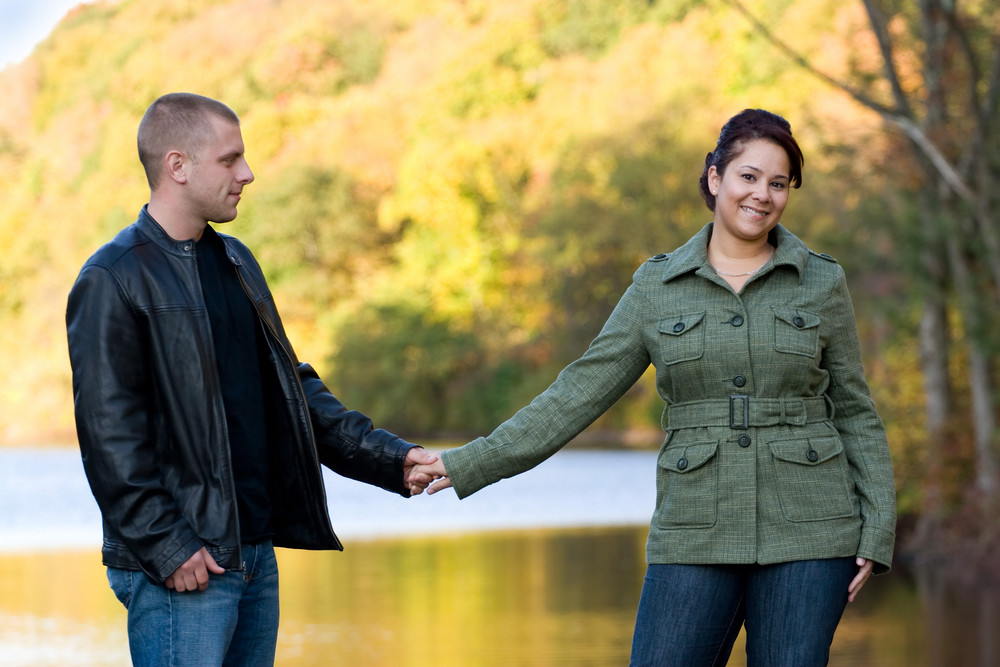 A young happy couple outdoors by a lake in autumn.