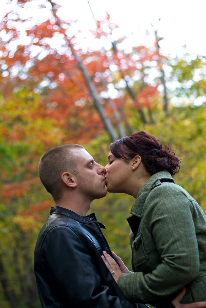 A young happy couple passionately kissing each other outdoors during fall or autumn.