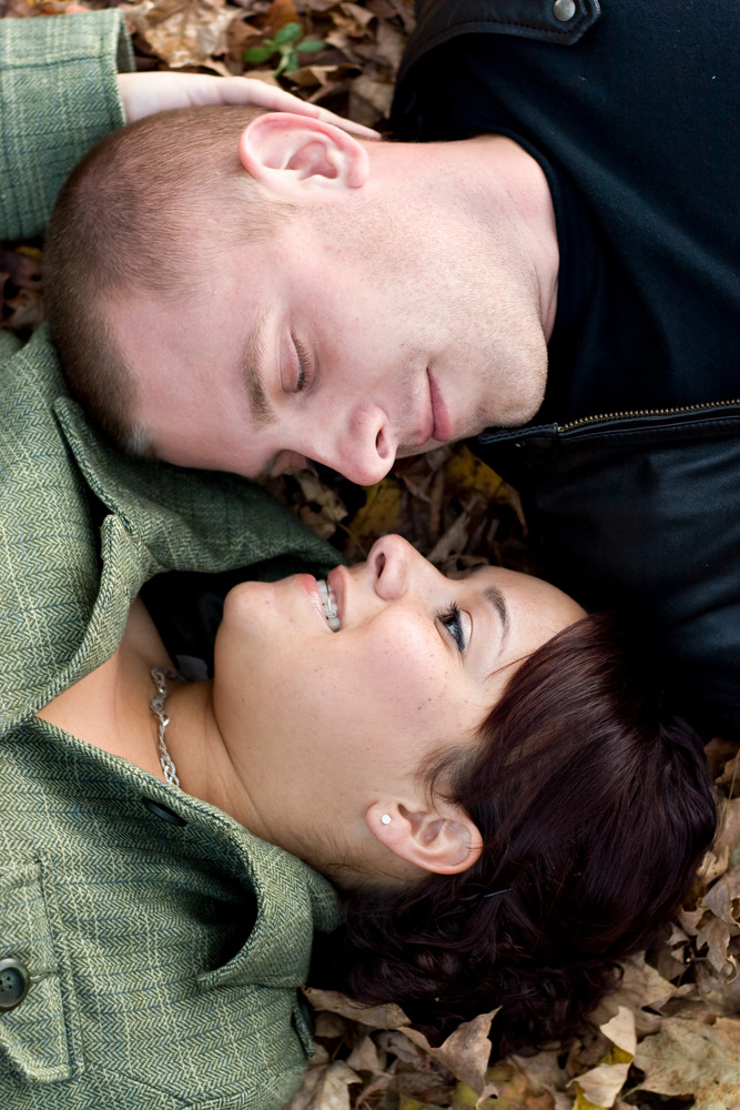 A young happy couple passionately kissing each other while laying in some autumn leaves.