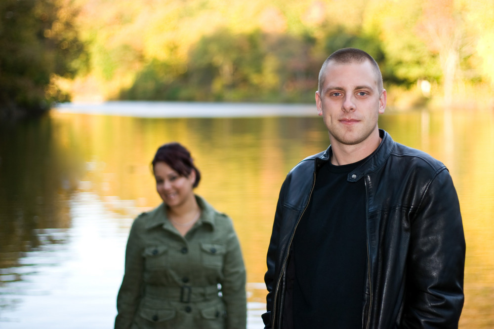 A young happy couple standing by a lake in autumn.  Shallow depth of field with focus on the man in the foreground.
