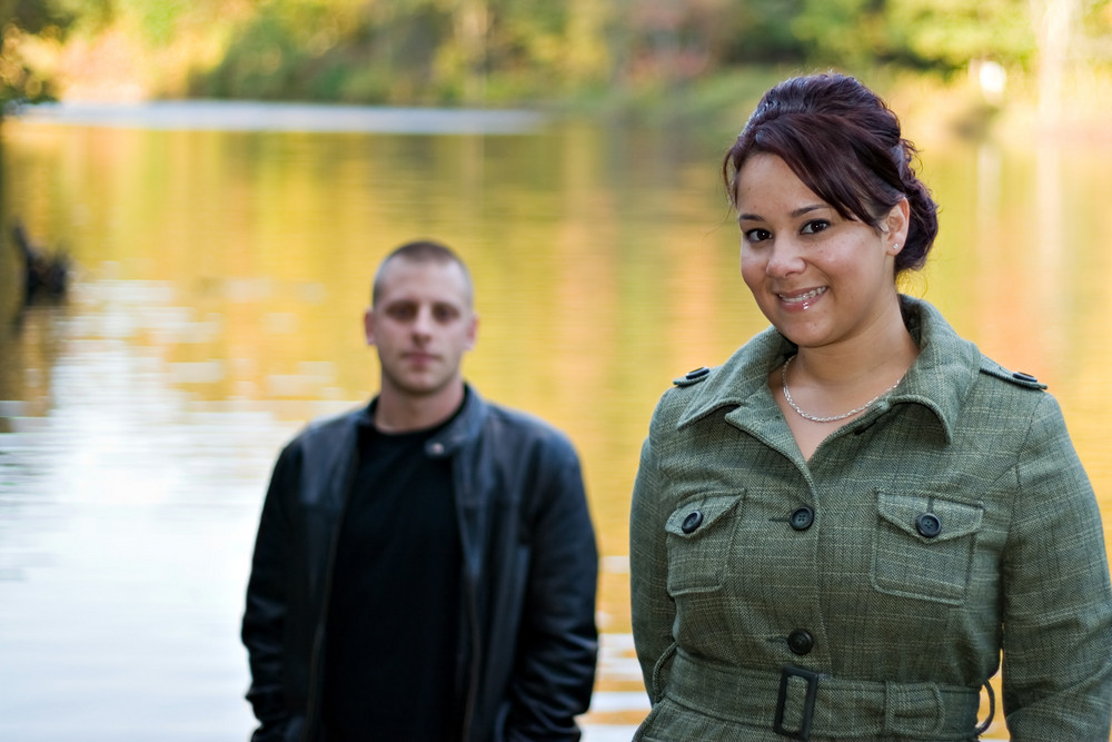 A young happy couple standing by a lake in autumn.  Shallow depth of field with focus on the woman.