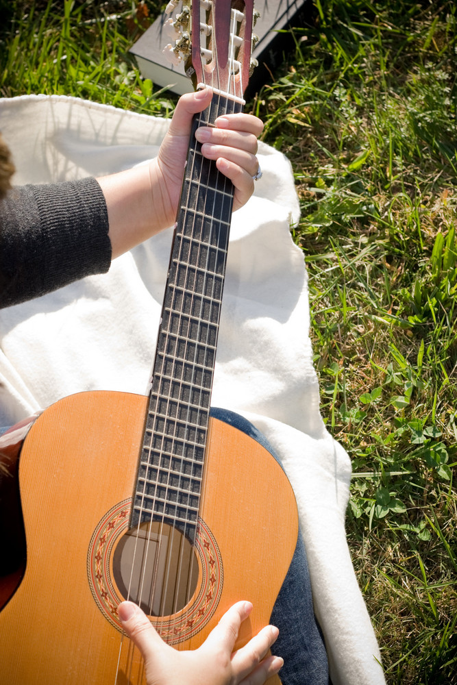 A young hispanic woman playing a guitar outdoors.