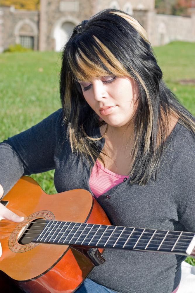 A young hispanic woman playing a guitar outdoors.