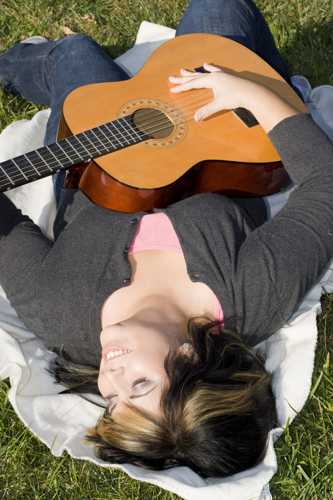 A young hispanic woman playing a guitar while laying on a blanket in the green grass.  Her hair is highlighted with blonde streaks.