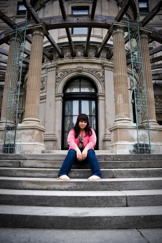 A young latin woman sitting on the steps of an old mansion.