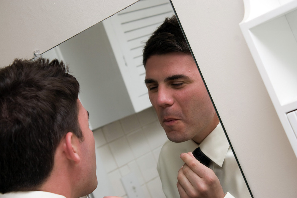 A young main in a shirt and tie checks his face in the bathroom mirror.