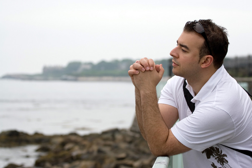 A young man doing some serious contemplation by the coast.