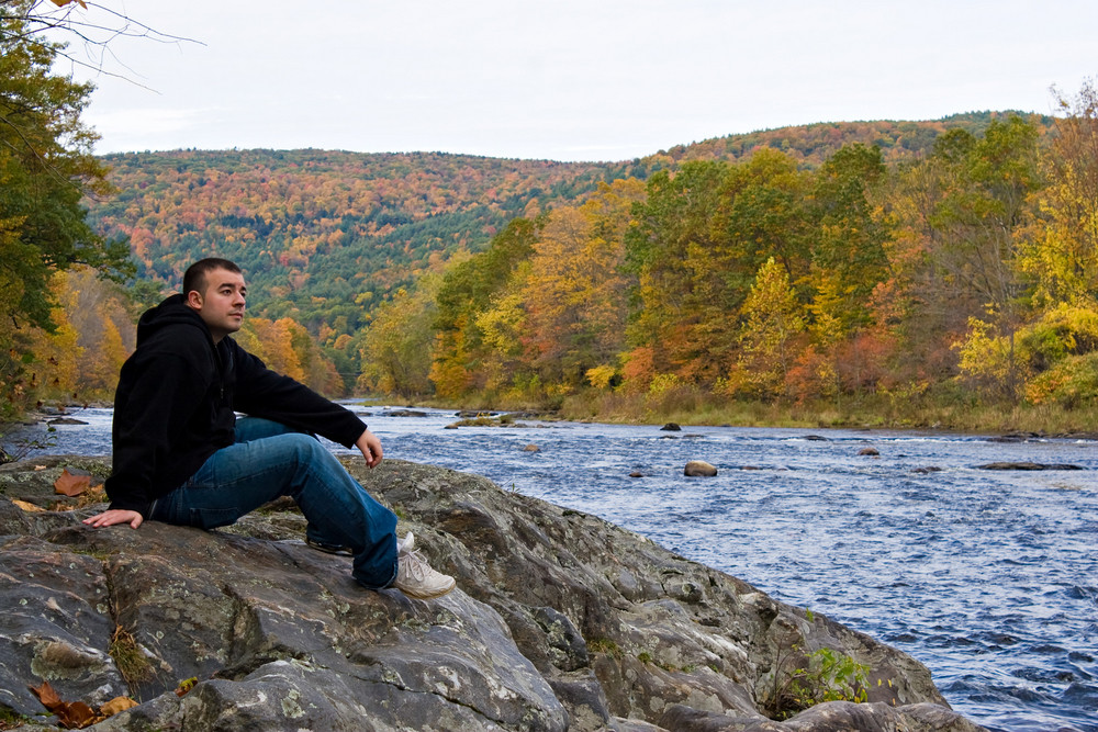 A young man enjoying the peaceful and beautiful sites and sounds of a Vermont river during peak Autumn foliage.