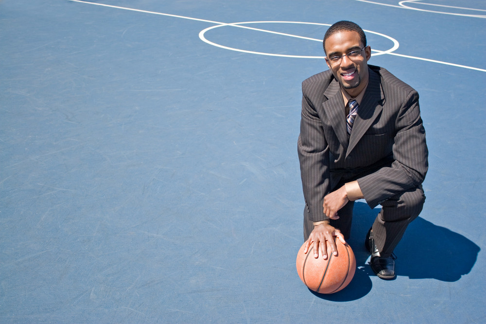A young man in a business suit posing in the empty basketball court with lots of copyspace.