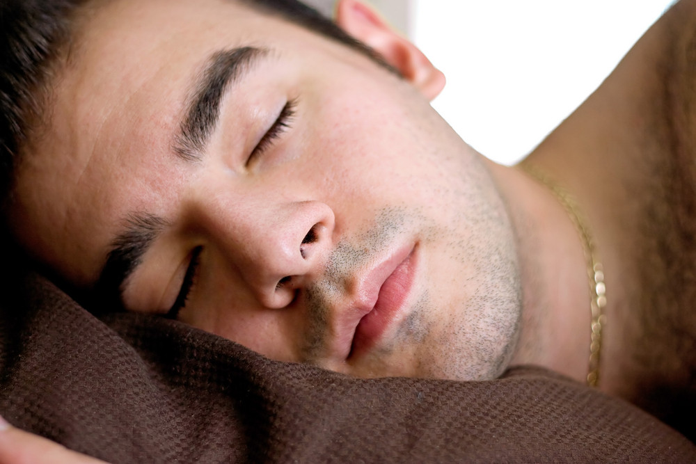 A young man is fast asleep in bed.