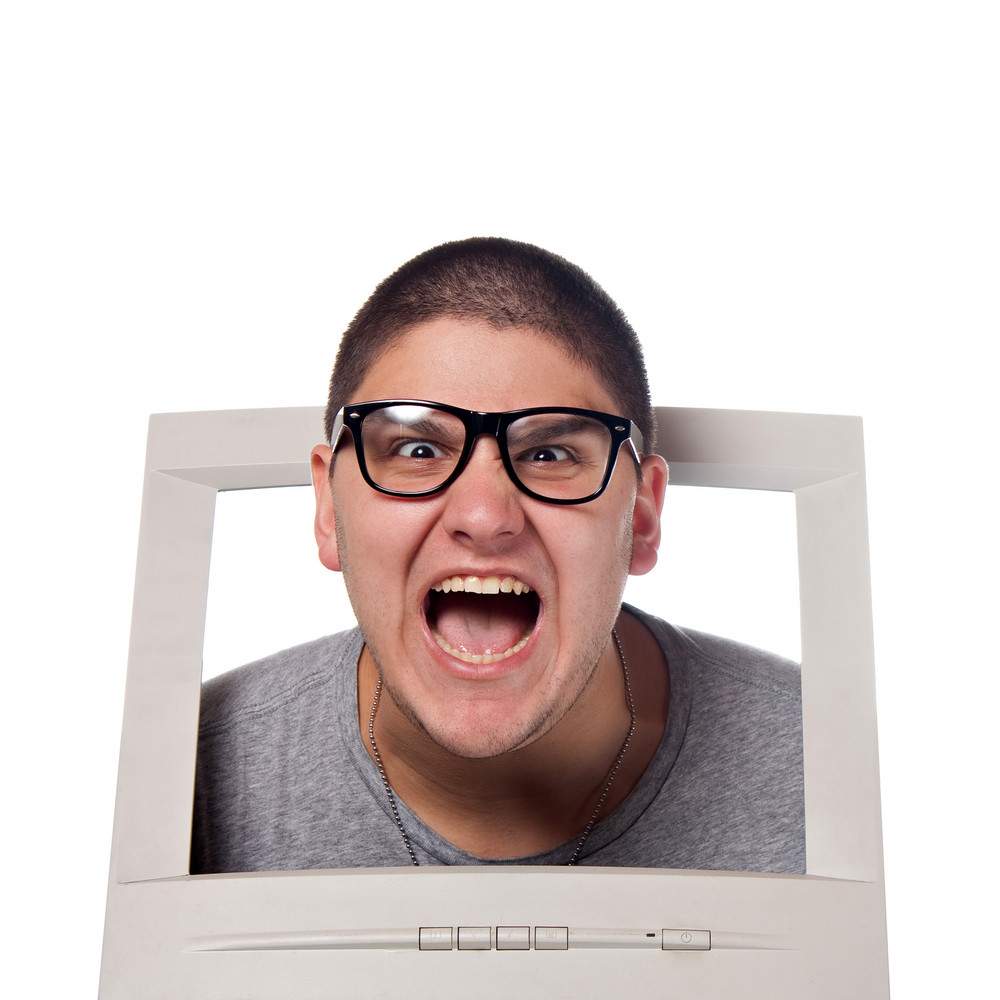 A young man popping his head out of a computer monitor with nerd glasses.