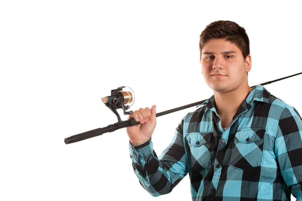 A young man poses with his fishing reel isolated over white in studio with negative space.
