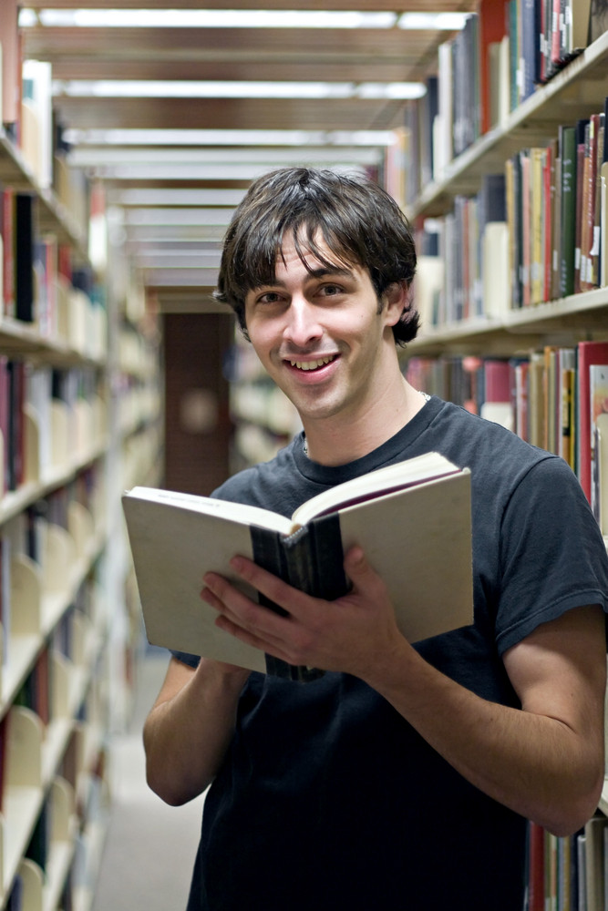 A young man reading a book at the library