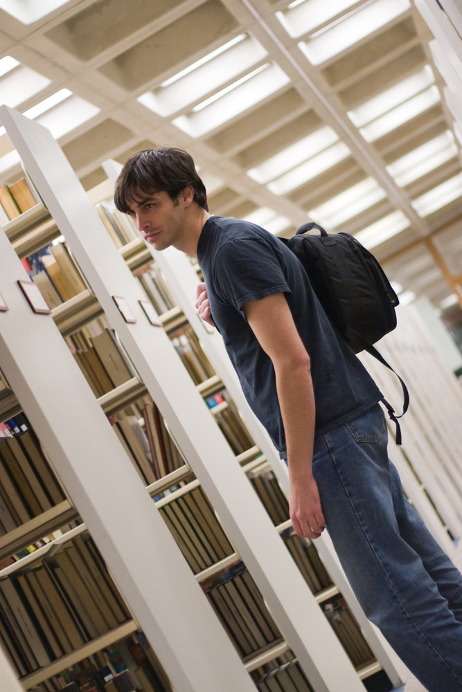A young man reads a book at the library while standing in the aisles of book shelves.