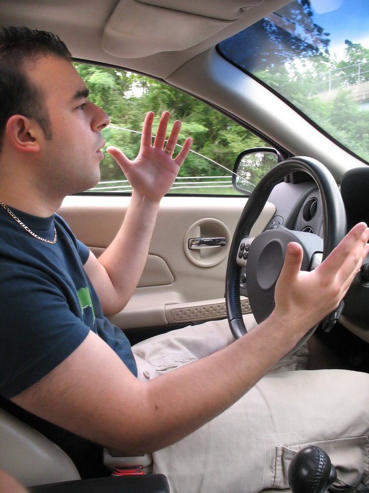 A young man seems to be experiencing some road rage while driving.