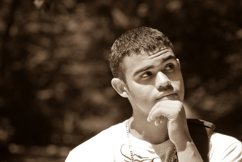 A young man that looks to be in deep thought.  He has something important on his mind.