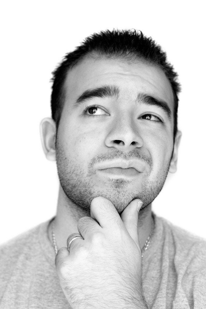 A young man with his hand on his chin thinking an important decision - black and white.