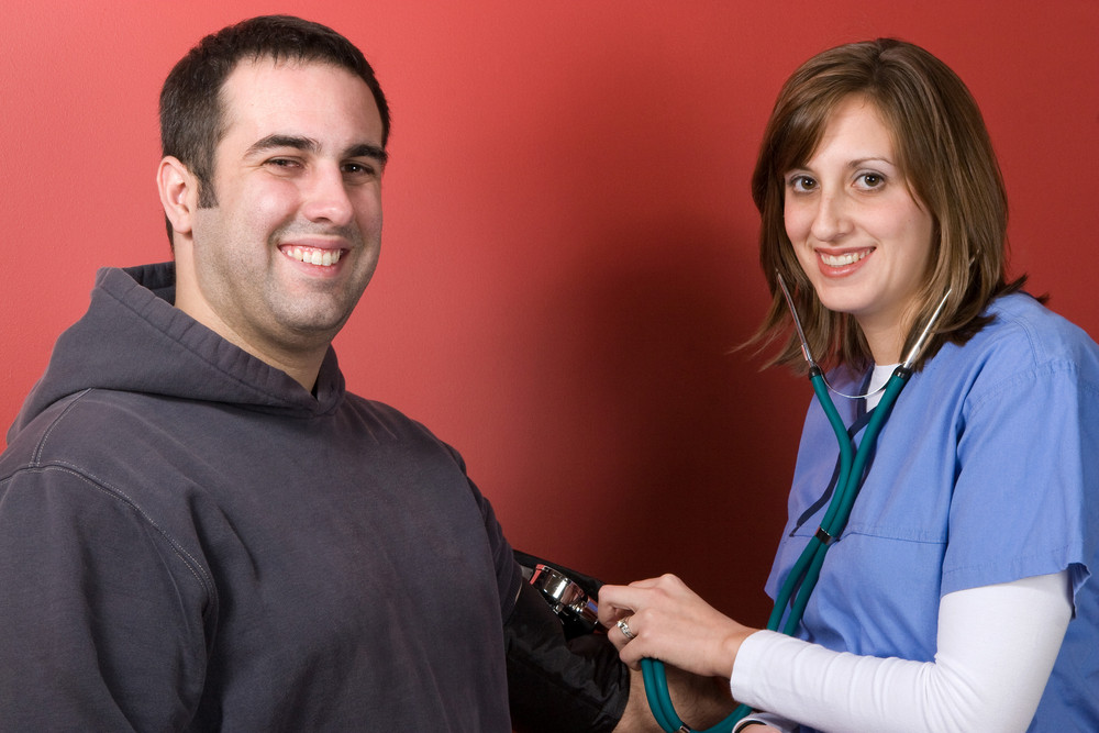 A young nurse checks the blood pressure of her patient.