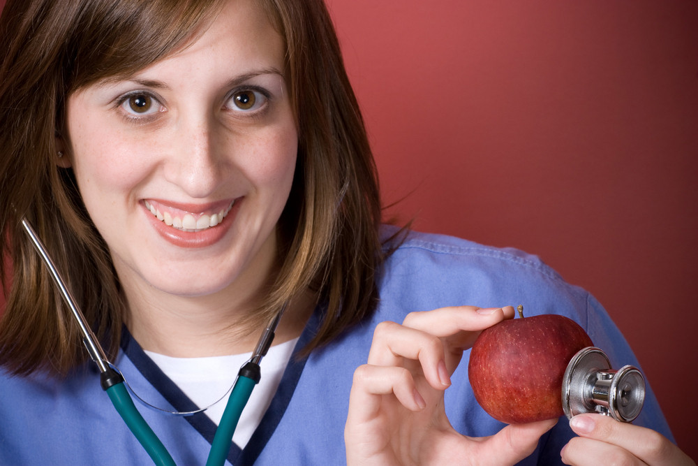 A young nurse is holding her stethoscope onto a red apple.  An apple a day keeps the doctor away.