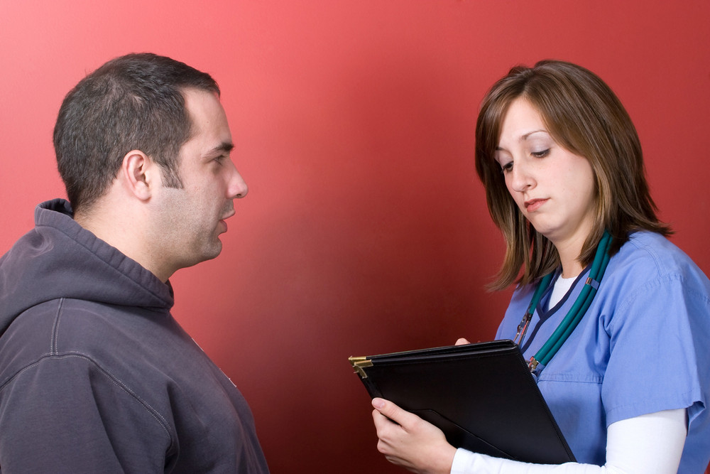A young nurse talks to a concerned patient during his visit.