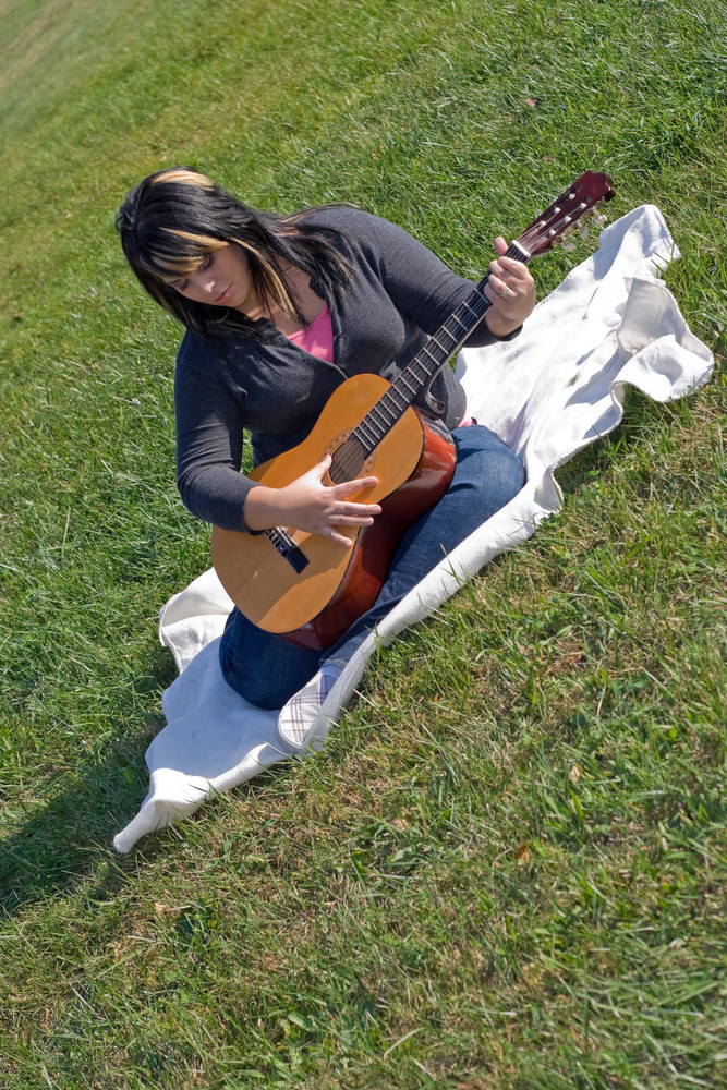 A young Spanish woman playing a guitar outdoors.