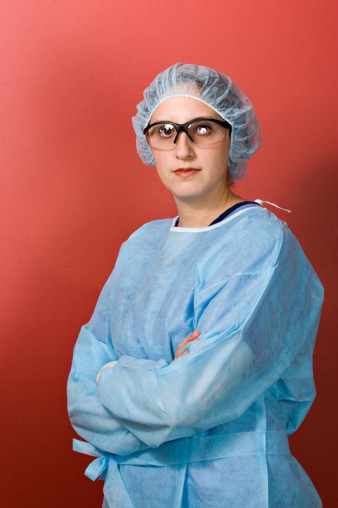 A young surgeon or nurse standing over a red background.