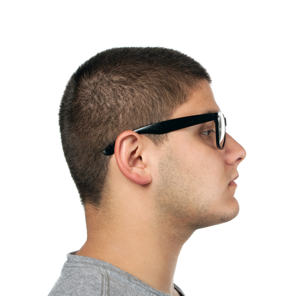 A young teenage man isolated over white wearing black frame nerd type vintage glasses.
