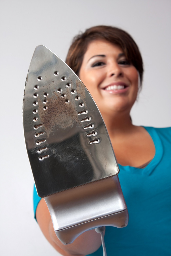A young woman at home holding up her household iron with a happy grin isolated over a silver background.