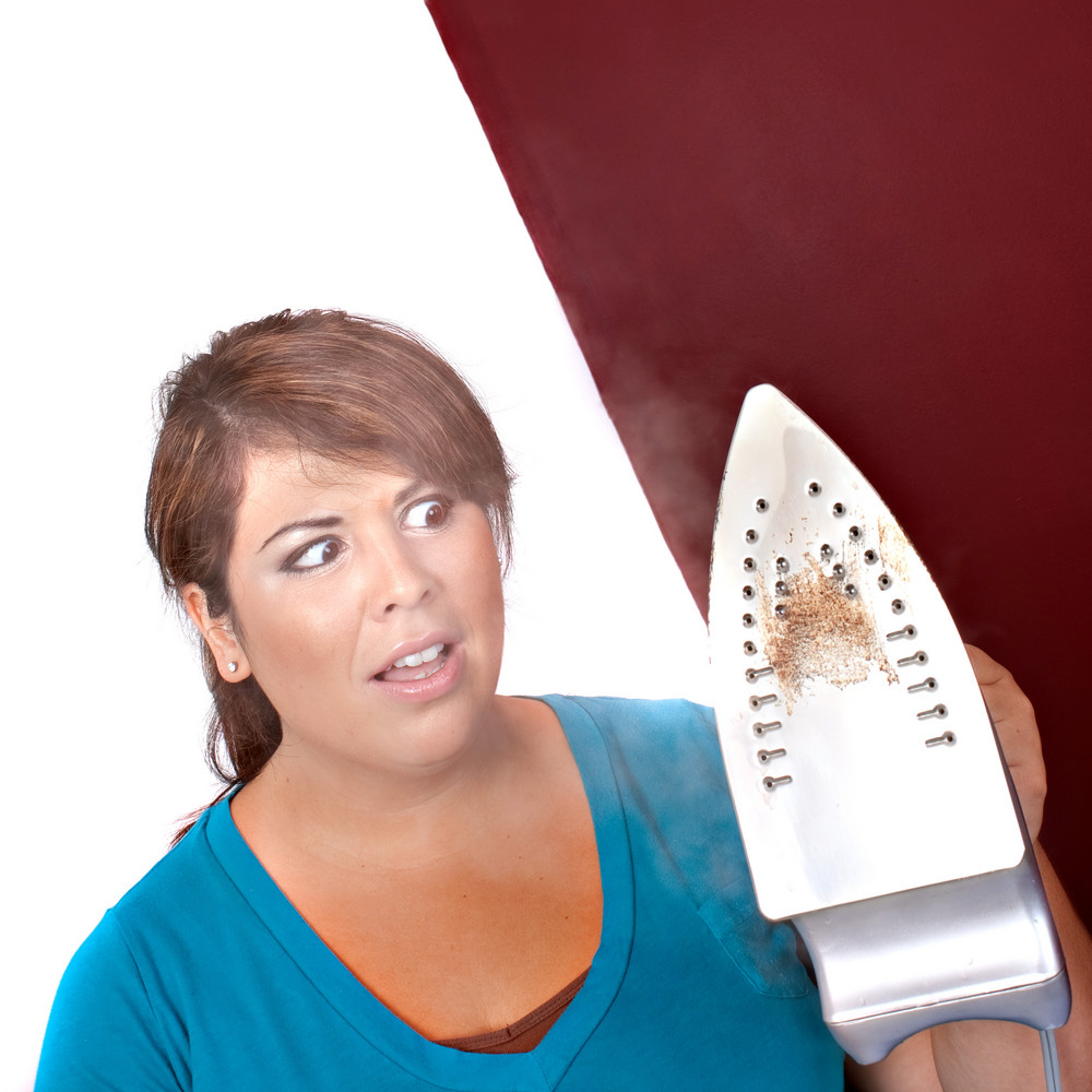 A young woman at home looking at her steaming household iron in disgust.