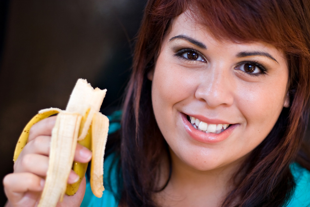 A young woman happily eating a banana.  Shallow depth of field with stronger focus on the face.