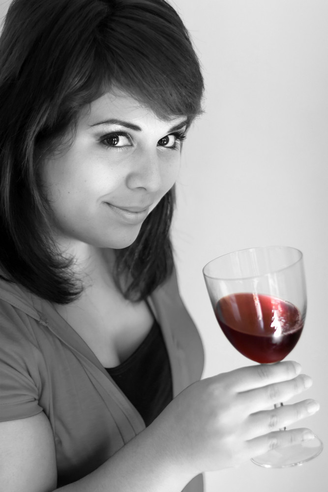 A young woman holding a glass of red wine. Selective color with emphasis on the red wine.