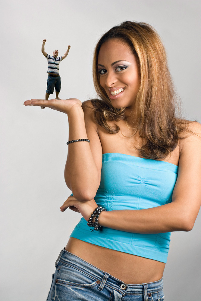 A young woman holding a miniature young man in her hand.