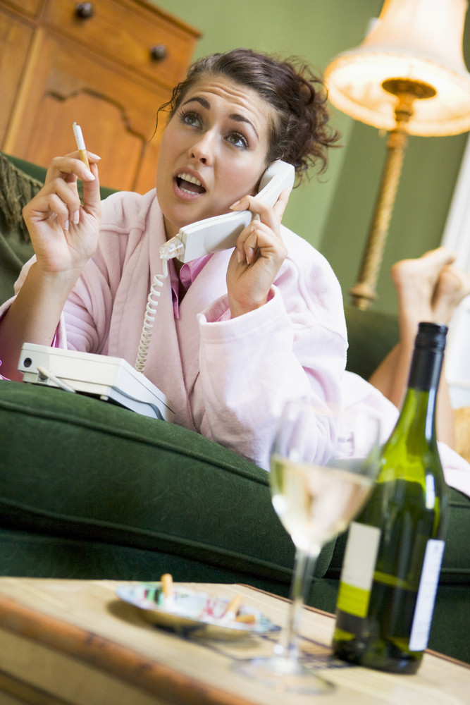A young woman in her pyjamas on the phone and smoking