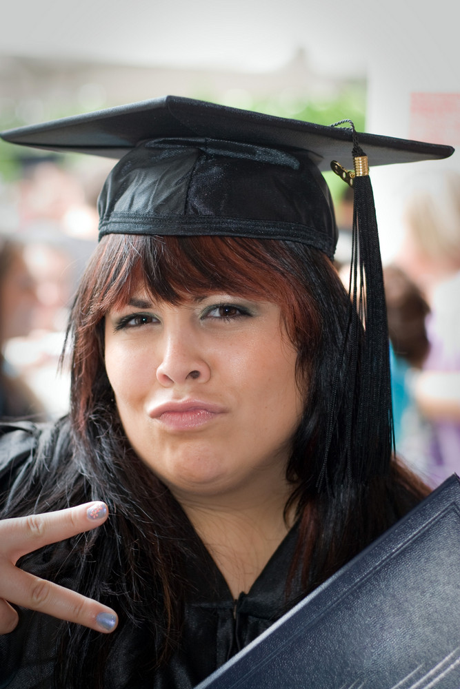 A young woman just receiving her diploma with a fun pose.
